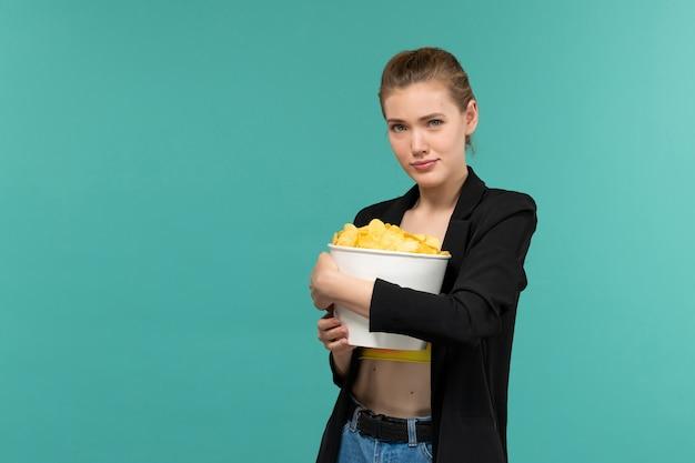 正面図若い魅力的な女性は、cipsを保持し、青い表面で映画を見ています