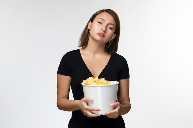 正面図白い表面にジャガイモのcipsとバスケットを保持している黒いシャツの若い魅力的な女性
