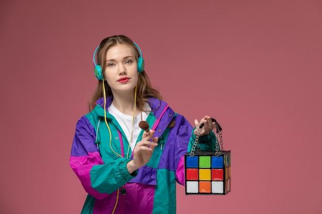 正面図濃いピンクの壁にメイクアップブラシを保持している色のコートの若い魅力的な女性モデル色女性の若い女の子