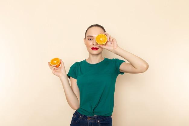 Вид спереди молодая привлекательная женщина в темно-зеленой рубашке, держащая апельсины на бежевом
