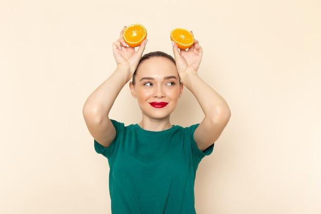 オレンジを保持している濃い緑色のシャツの正面若い魅力的な女性