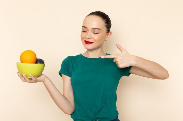 正面を向いた果物とプレートを保持している濃い緑のシャツの若い魅力的な女性の正面図