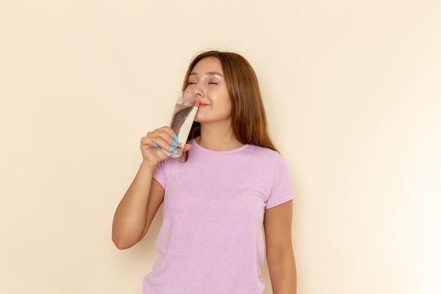 Вид спереди молодая привлекательная женщина в розовой футболке и синих джинсах пьет воду с довольным выражением лица ¡