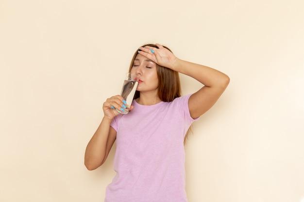 Вид спереди молодая привлекательная женщина в розовой футболке и синих джинсах с питьевой водой
