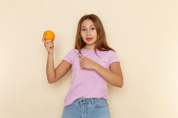 ピンクのtシャツとブルージーンズを保持し、オレンジを指している若い魅力的な女性の正面図¡