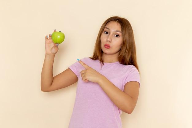 ピンクのtシャツとブルージーンズのリンゴを押しながらそれを指している正面の若い魅力的な女性