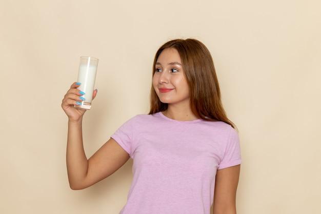 Вид спереди молодая привлекательная женщина в розовой футболке и синих джинсах, держащая стакан молока