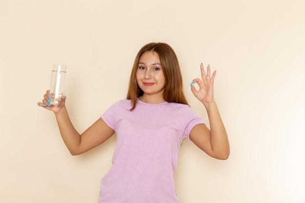 Вид спереди молодая привлекательная женщина в розовой футболке и синих джинсах, держащая стакан воды с улыбкой