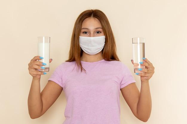 Вид спереди молодая привлекательная женщина в розовой футболке и синих джинсах, держащая стаканы воды и молока в маске