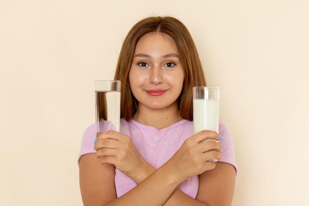 Вид спереди молодая привлекательная женщина в розовой футболке и синих джинсах, держащая стаканы воды и молока с улыбкой