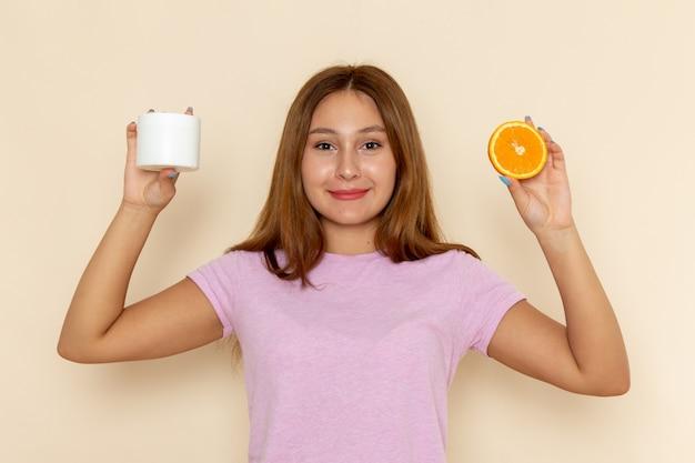 Вид спереди молодая привлекательная женщина в розовой футболке и синих джинсах с оранжевым