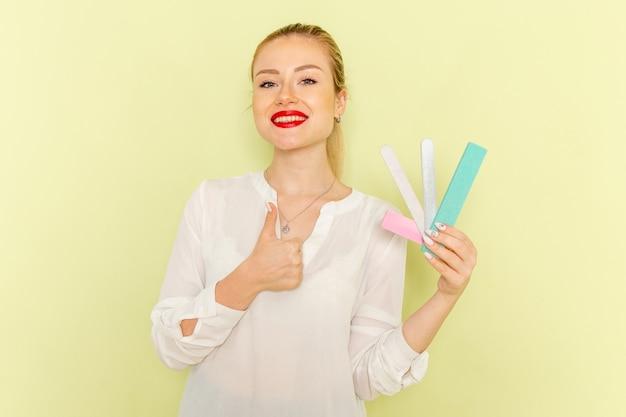 녹색 책상에 다른 매니큐어 액세서리를 들고 흰 셔츠에 전면보기 젊은 매력적인 여성