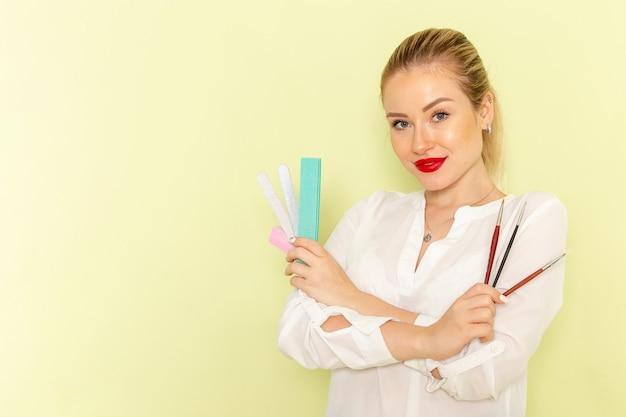 녹색 표면에 술과 매니큐어 액세서리를 들고 흰 셔츠에 전면보기 젊은 매력적인 여성