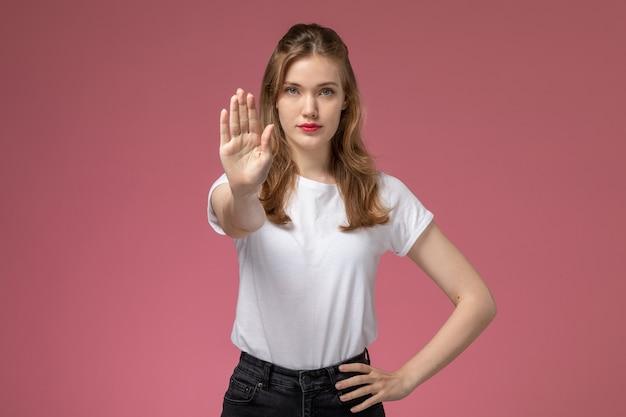 Вид спереди молодая привлекательная женщина в белой футболке и черных брюках, позирующая эффектный знак остановки на розовой стене, модель, женская поза, цветное фото
