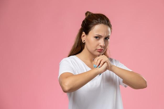 ピンクの背景の白いtシャツの怒りの表現で正面の若い魅力的な女性