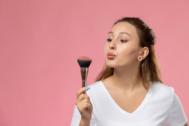 Вид спереди молодая привлекательная женщина в белой футболке, сдувающая кисть для макияжа на розовом фоне