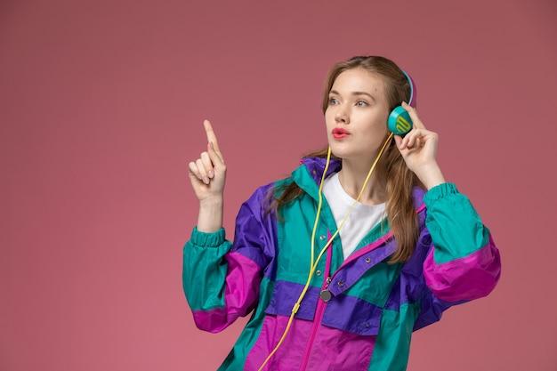 ピンクの壁のモデルの女性のポーズの色の女性の若いで音楽を聴いている白いtシャツ色のコートの正面図若い魅力的な女性