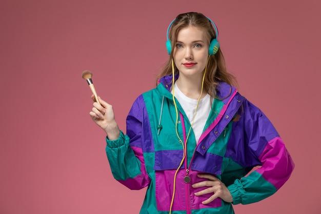 Вид спереди молодая привлекательная женщина в белой футболке цветного пальто, слушающая музыку через наушники на розовой стене, модель женского цвета позы