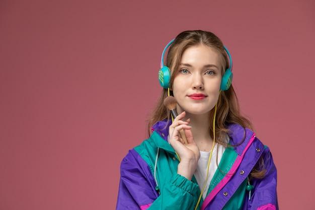 ピンクの壁のモデルの女性のポーズのカラー写真でイヤホンを介して音楽を聴いている白いtシャツ色のコートで若い魅力的な女性の正面図