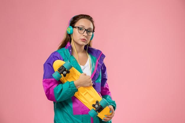 분홍색 배경에 스케이트 보드와 함께 포즈 흰색 티셔츠 컬러 코트에 전면보기 젊은 매력적인 여성