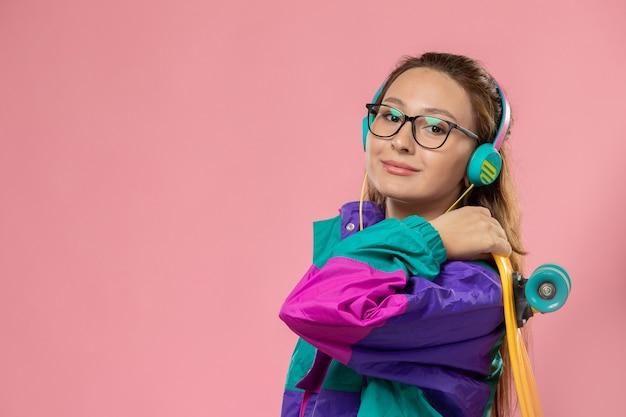 白いtシャツのコートの笑顔とピンクの背景にスケートボードを保持している正面の若い魅力的な女性