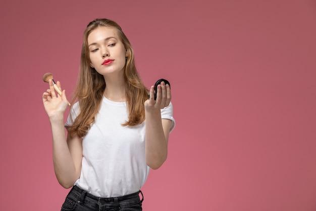 ピンクの壁のモデルの色の若い女性の化粧をしている白いtシャツの正面図若い魅力的な女性