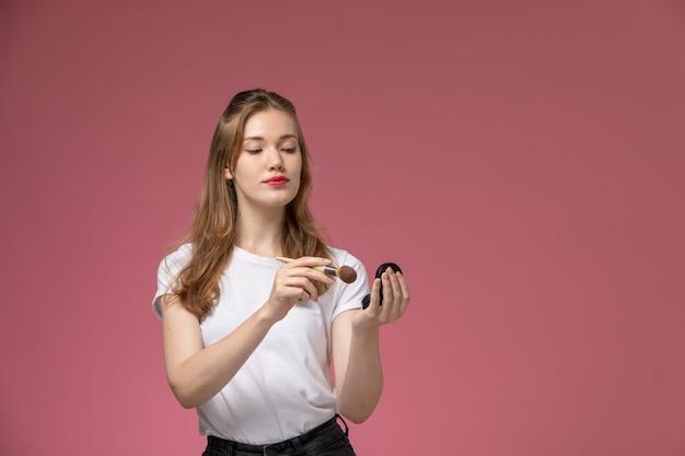 ピンクの壁モデルの女性のポーズのカラー写真にブラシで化粧をしている白いtシャツの若い魅力的な女性の正面