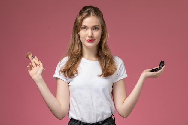 ピンクの壁に笑顔でメイクをしている白いtシャツの正面図若い魅力的な女性モデル色女性若い