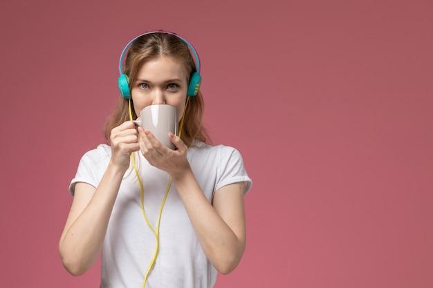 ピンクの壁のモデルカラーの若い女性の音楽を聴いてお茶を飲む白いtシャツの正面図若い魅力的な女性