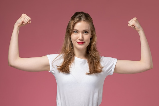 ピンクの机のモデルの色の女性の若い女の子に屈曲する白いtシャツの正面図若い魅力的な女性