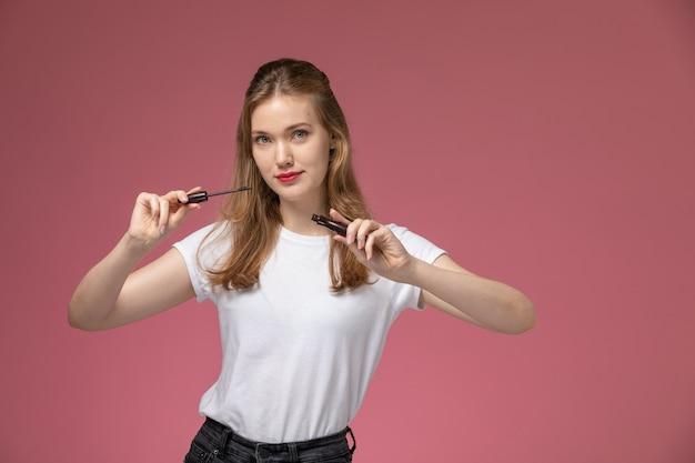 핑크 데스크 모델 색상 여성 어린 소녀에 눈 마스카라를 들고 흰색 티셔츠에 전면보기 젊은 매력적인 여성