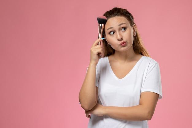 ピンクの背景に化粧ブラシを保持している白いtシャツの正面若い魅力的な女性