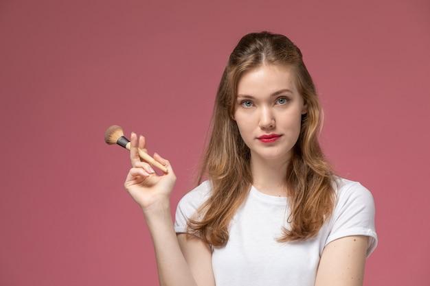 ピンクの壁に化粧ブラシを保持している白いtシャツの正面図若い魅力的な女性モデル色女性若い