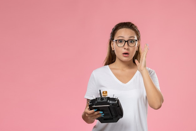Вид спереди молодая привлекательная женщина в белой футболке с пультом дистанционного управления на розовом фоне