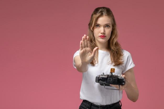 Вид спереди молодая привлекательная женщина в белой футболке с пультом дистанционного управления, показывающая знак остановки на розовой стене, цвет модели, молодая женщина