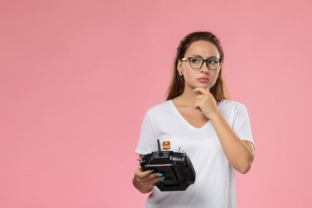 Вид спереди молодая привлекательная женщина в белой футболке, держащая пульт дистанционного управления с выражением мышления на розовом фоне