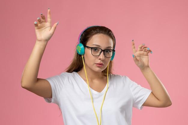 正面ポーズし、イヤホンを介して音楽を聴いて、ピンクの机の上で踊ろうとする白いtシャツの若い魅力的な女性