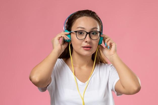 正面と白いtシャツの若い魅力的な女性の正面とピンクの背景にイヤホンを介して音楽を聴くだけ