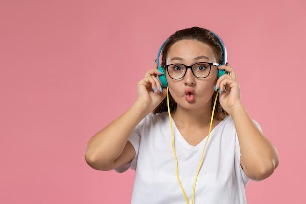Вид спереди молодая привлекательная женщина в белой футболке, просто позирует и слушает музыку через наушники на розовом фоне