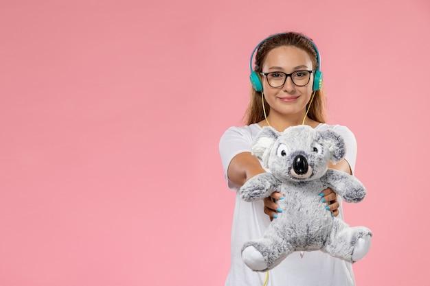 Вид спереди молодая привлекательная женщина в белой футболке, слушающая музыку, держа игрушку на розовом фоне