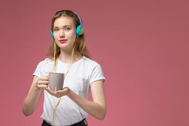 핑크 벽 모델 색상 여성 젊은에 컵을 들고 음악을 듣고 흰색 티셔츠에 전면보기 젊은 매력적인 여성