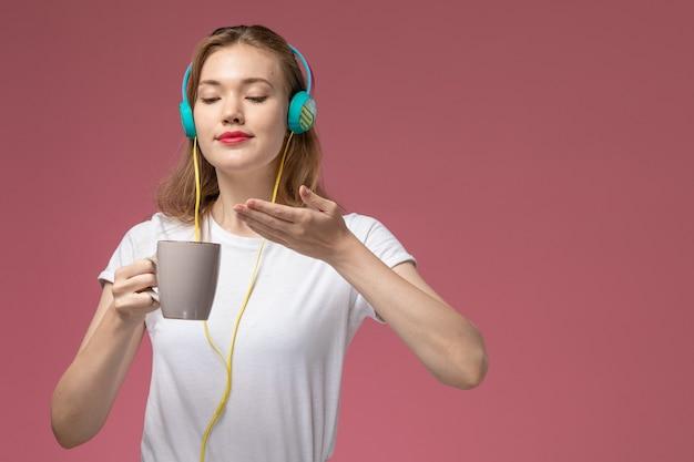 ピンクの机の上でお茶を飲むイヤホンで音楽を聴く白いtシャツの正面図若い魅力的な女性モデル色女性若い