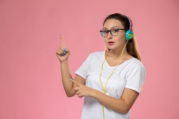 ピンクの背景にイヤホンで音楽を聴く白いtシャツの正面の若い魅力的な女性
