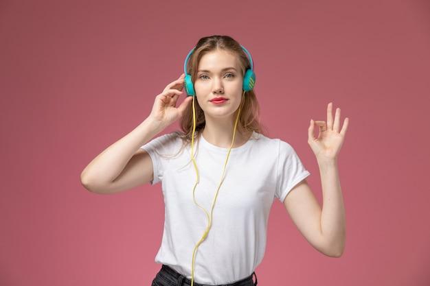 ピンクの机のモデルの色の女性の若い女の子の彼女のヘッドフォンで音楽を聴いている白いtシャツの正面図若い魅力的な女性