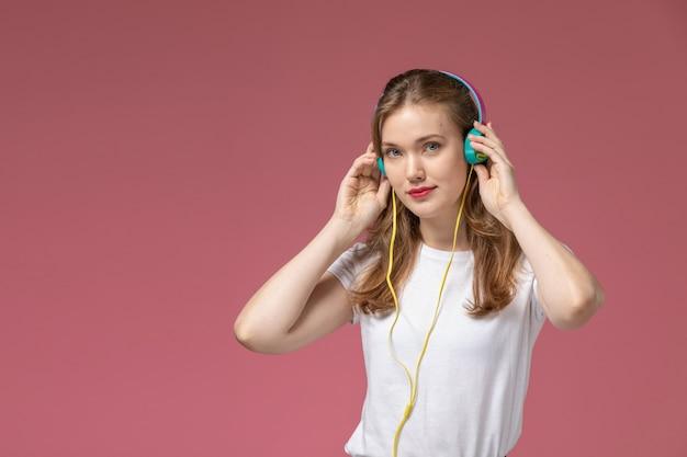 어두운 분홍색 책상 모델 색상 여성 어린 소녀에 미소로 음악을 듣고 흰색 티셔츠에 전면보기 젊은 매력적인 여성