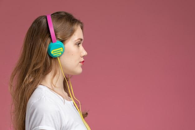 濃いピンクの壁のモデルカラーの女性の若い女の子に髪を向けて音楽を聴いている白いtシャツの正面図若い魅力的な女性