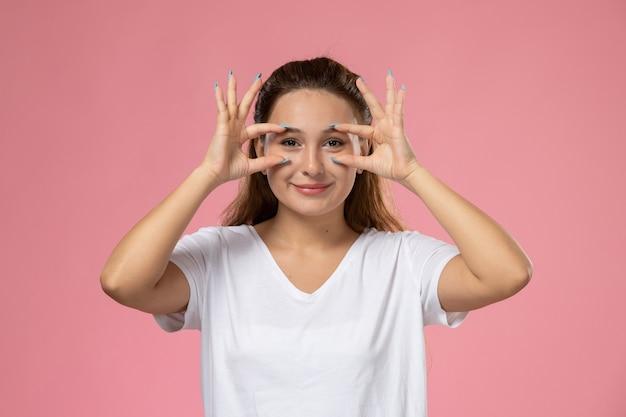 ピンクの背景に白いtシャツのポーズとsmiで正面の若い魅力的な女性