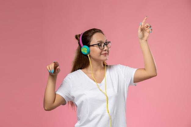 白いtシャツのヘッドフォンで音楽を聴くポーズとピンクの背景に笑顔で正面の若い魅力的な女性