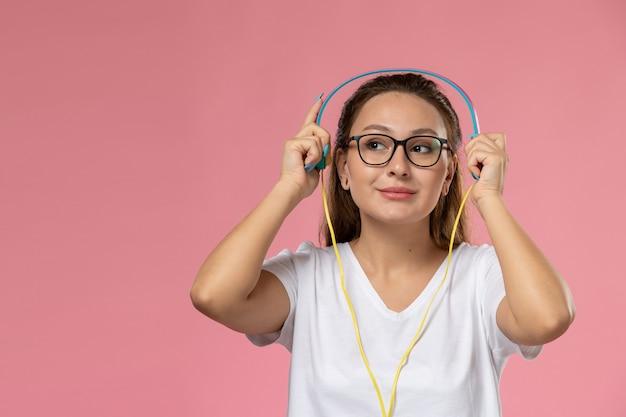 Вид спереди молодая привлекательная женщина в белой футболке позирует, слушая музыку в наушниках smi на розовом фоне