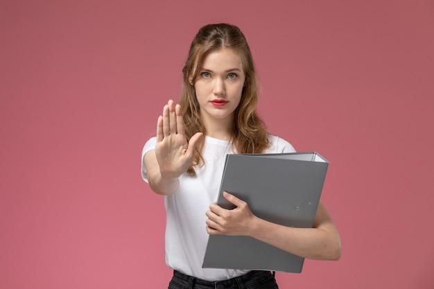 Вид спереди молодая привлекательная женщина в белой футболке позирует с серым файлом, показывающим знак остановки на розовой стене, цвет модели